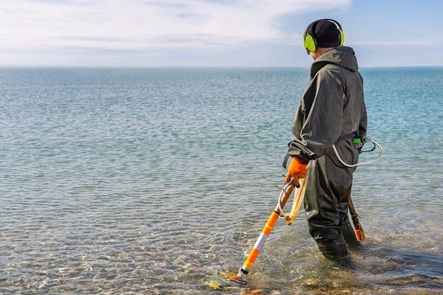 Мужчина стоит по колено в воде и ищет драгоценные металлы с помощью металлоискателя