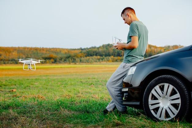 車の近くに立っている男性がドローンを発射します。黄色いフィールドでのドローン飛行