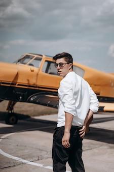 小さな単一のエンジン飛行機の背景に立っている男。