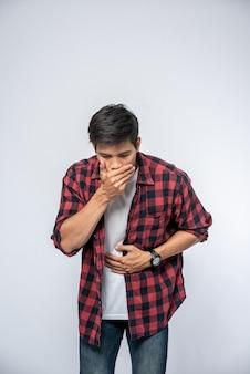 腹痛で立っている男性手を胃に当てて口を覆います。