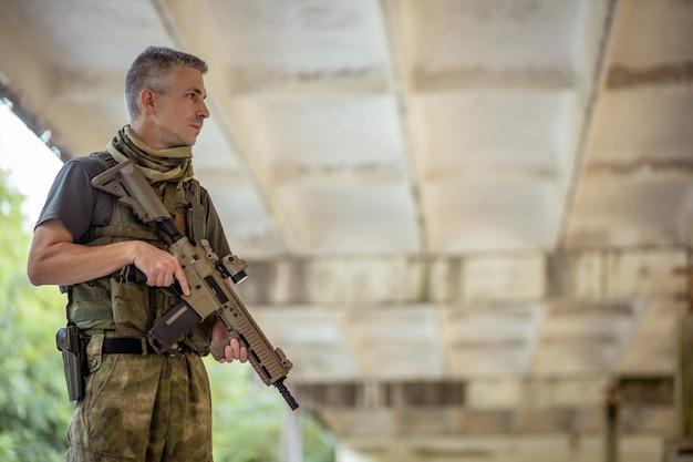 コンクリート格納庫の軍服でエアガンアサルトライフルを持って立っている男