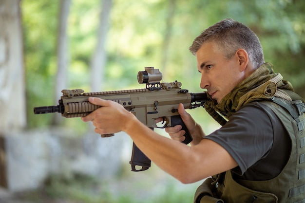 森の中で軍服を着たエアガンアサルトライフルを持って立っている男