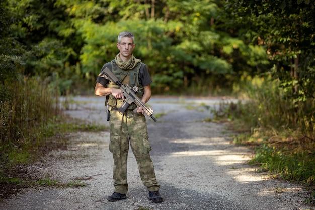 軍服を着たエアガンのアサルトライフルを持って立っている男
