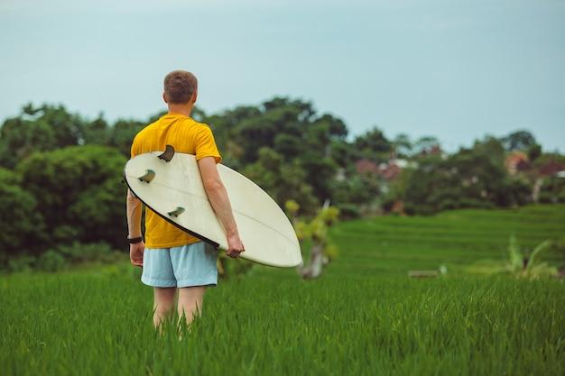 Мужчина стоит на рисовом поле.