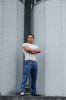 Мужчина стоит перед техническими сооружениями. возможности и перспективы