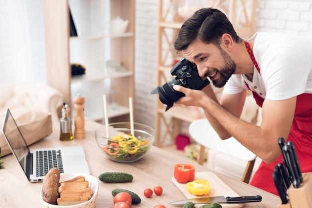 Мужчина стоит на кухне, фотографирует на кухне.