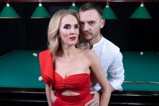 男はビリヤード台に寄りかかって立って、ブロンドの髪とゴージャスなバストでセクシーな女性を優しく抱きしめます