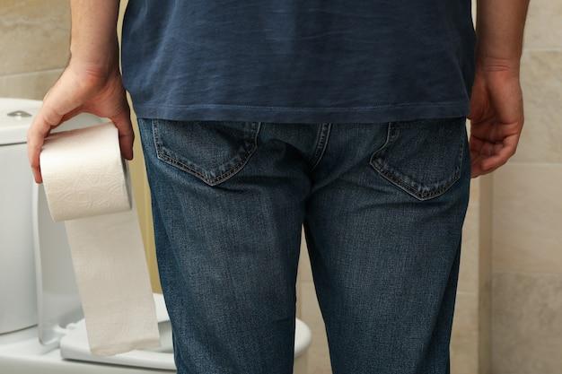 男がトイレの近くに立ってトイレットペーパーを持っている
