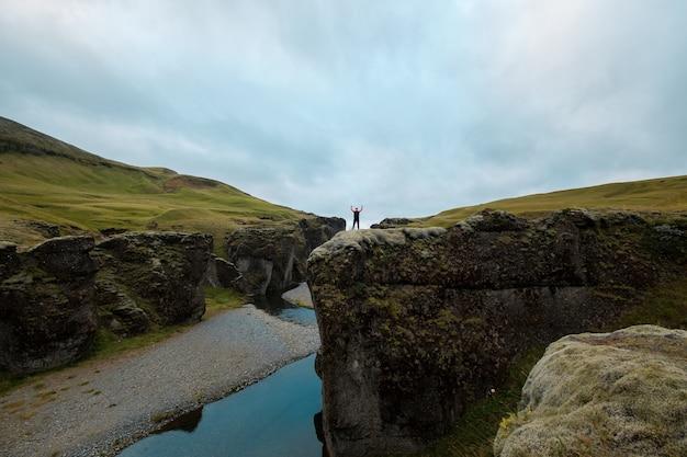 한 남자가 손을 들고 언덕 위에 서 있습니다. 아이슬란드 풍경입니다.