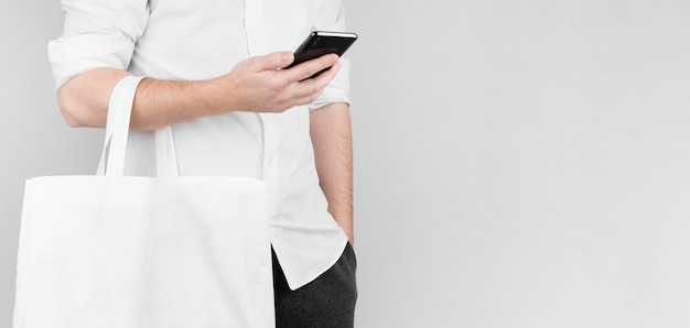 男は白い背景の上に立ち、電話でニュースを読み、ひじに亜麻でできたエコバッグを持っています。エコロジーコンセプト