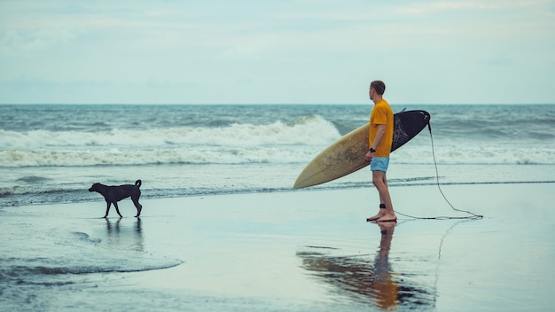 男はサーフボードを持ってビーチに立っています。