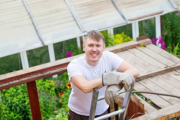 男が階段に立って、カメラに向かって休んで笑っている。屋根を解体する。