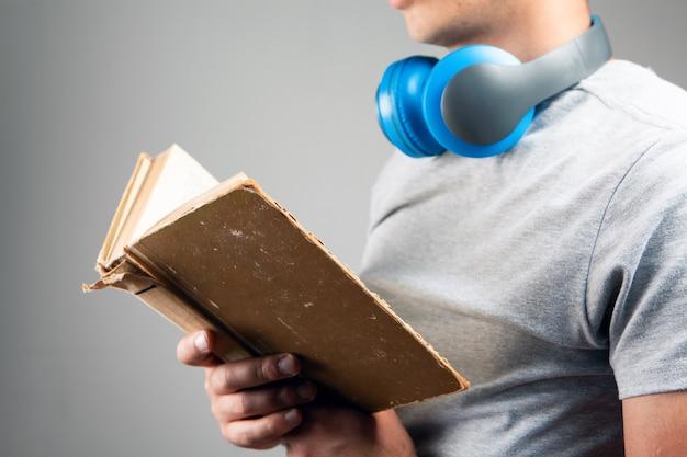 남자는 책과 헤드폰으로 서 있습니다. 오디오 북