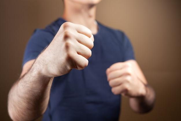 남자는 갈색 배경에 싸우는 자세에 주먹으로 서