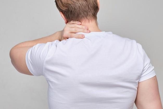 白いtシャツを着た男が背を向けて立ち、激しい痛みのために首をつかみます。マッサージ。