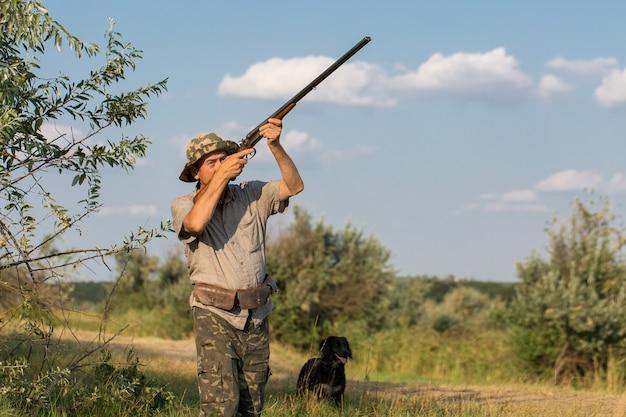 男は武器と狩猟犬と一緒に立ってゲームを追跡します