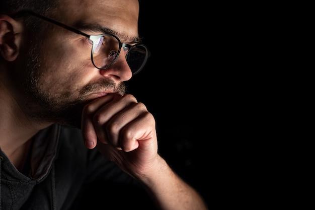 男は夜の暗闇の中でコンピューターの画面をじっと見つめ、スペースをコピーします。