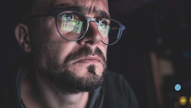 男は夜、暗闇の中でコンピューターの画面をじっと見つめる