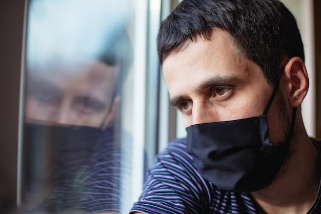 隔離中の男性は隔離されたまま家にいます。コロナウイルスパンデミック。男は窓から通りを見つめる