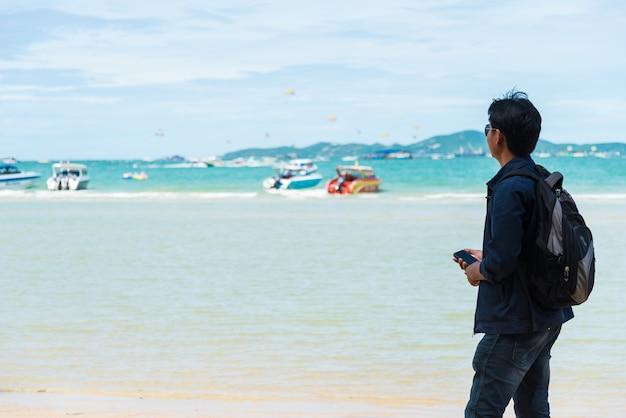 男はビーチでボートに乗るのを待っていた。