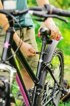 Мужчина поправляет, ремонтирует сиденье горного велосипеда на лесной дороге
