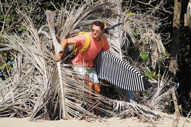 오두막에서 서핑 보드와 함께 남자 서퍼. 해변 서핑 장소.