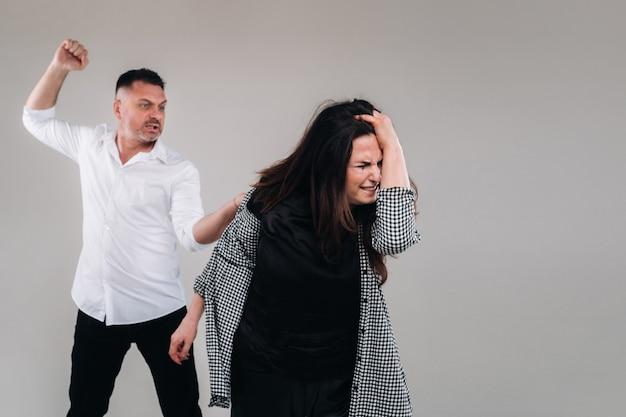 한 남자가 회색 배경에 서 있는 구타당한 여성에게 주먹을 휘두른다. 가정 폭력