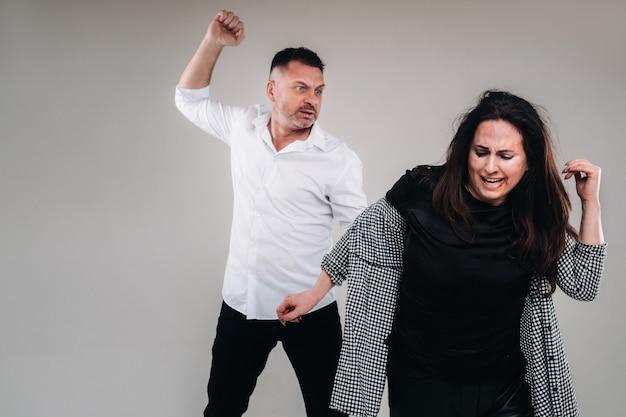 Мужчина машет рукой на избитую женщину, стоящую на сером фоне. домашнее насилие.