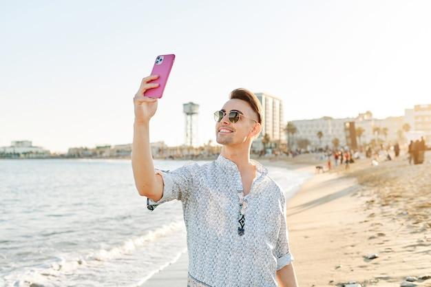 携帯電話で自分撮りをしている男性