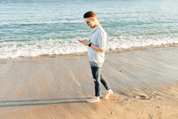 해변에서 전화 통화하는 남자