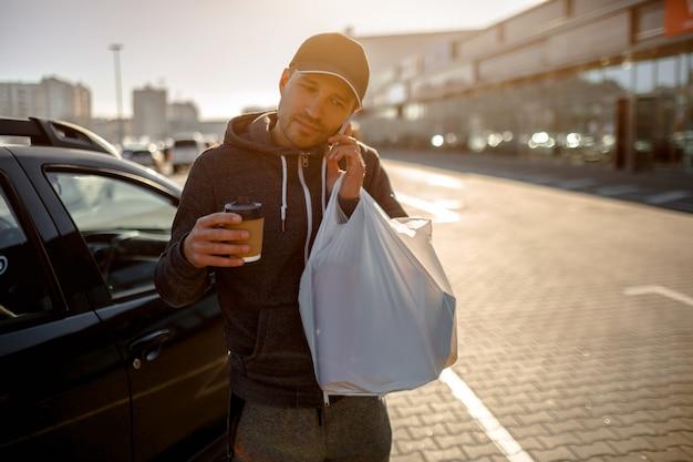 男は電話で話し、食品、野菜、果物、乳製品が入った食品の袋を持っています。ショッピングセンターやショッピングモールの近くの駐車場に立っている男性。