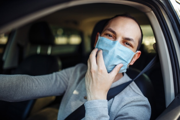 한 남자 택시 기사가 차를 운전하고 코로나 바이러스가 발생하는 동안 의료 마스크를 조정합니다.
