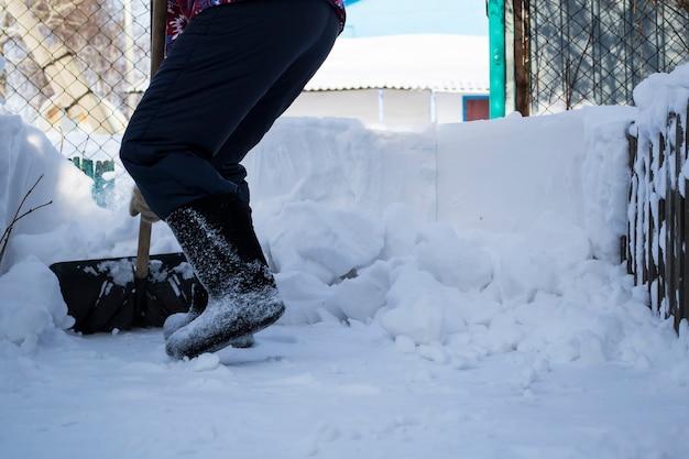 雪の中に立っている男少女は足で雪をきれいにする