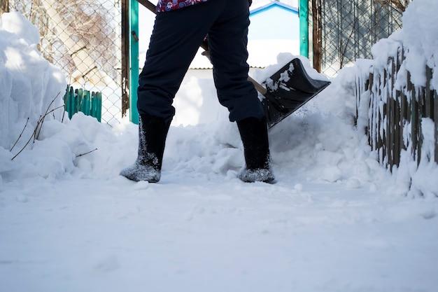 雪の中に立っている男少女は足で雪をきれいにする Premium写真