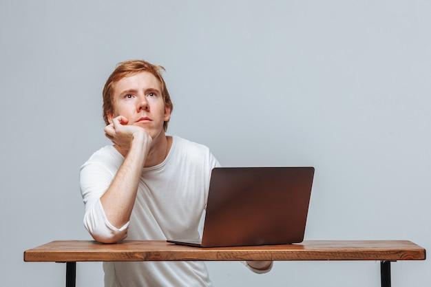 Человек думает за ноутбук на светлом фоне
