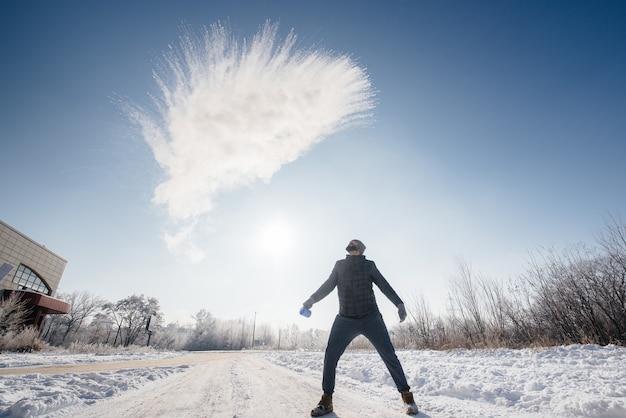 男は寒さの中で沸騰したお湯を投げ出し、それは即座に蒸気に変わります。お湯のトリック。