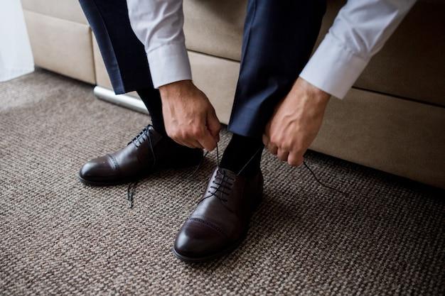 Мужчина завязывает шнурки на туфлях утром в комнате