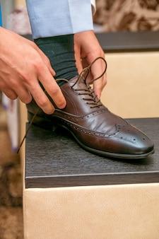 男は部屋の茶色の靴に靴ひもを結びます
