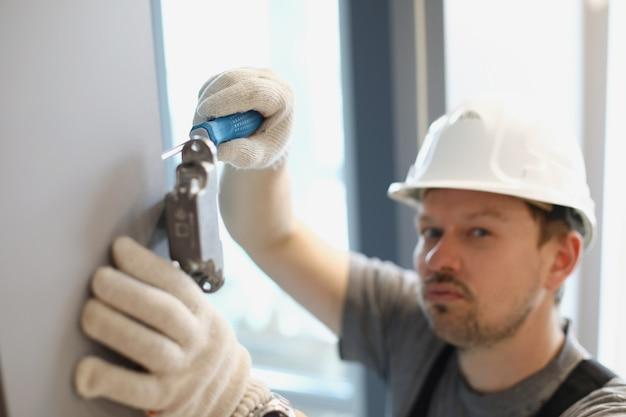 男は、キャビネットドアのドライバー修理で金属製の付属品を締めます