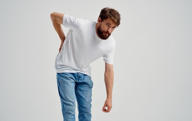 Мужчина трогает спину рукой, болезненно ощущает недомогание в позвоночнике.
