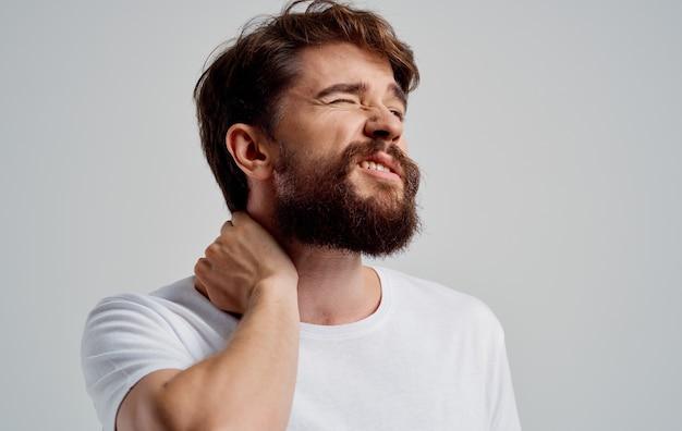 한 남자가 손으로 목을 만집니다. 척추의 골 연골 증 통증. 고품질 사진