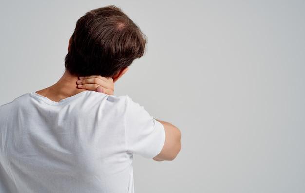 남자가 손으로 목을 만집니다. 척추의 골 연골 증 통증