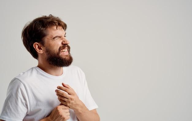 한 남자가 빛과 흰색 티셔츠에 손목을 만집니다.