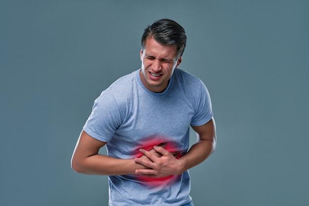복사 공간이 있는 회색 배경에 배를 만지는 남자. 위 통증 및 기타 위장 질환 개념.