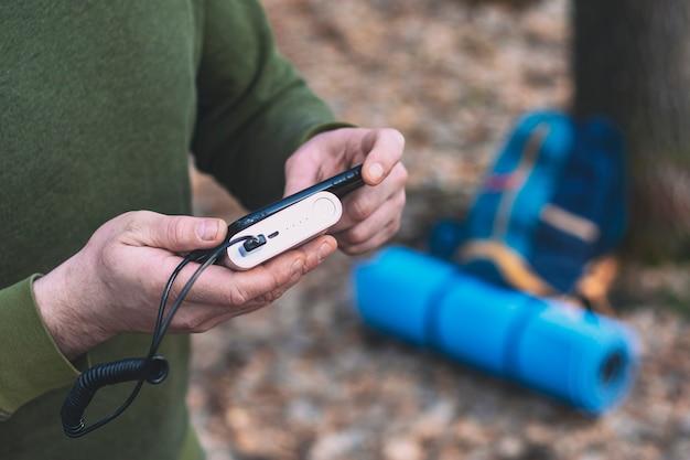 한 남자 관광객이 스마트 폰을 손에 들고 파워 뱅크로 충전합니다. 배낭과 숲에서 관광 깔개.