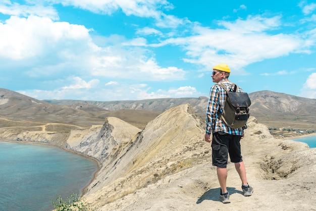 배낭을 메고 있는 한 남자 관광객이 산꼭대기에 서서 아름다운 바다 전망을 즐깁니다. 여행 컨셉