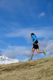 한 남자가 가을에 산에 첫 눈이 내리는 산에서 울트라 런 트레일을 위해 훈련합니다.