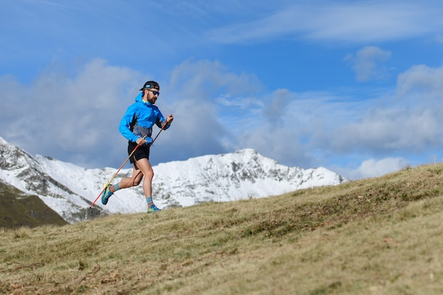 한 남자가 산에 첫 눈이 내리는 가을에 언덕이 많은 초원에서 울트라 런 트레일을 위해 훈련합니다.