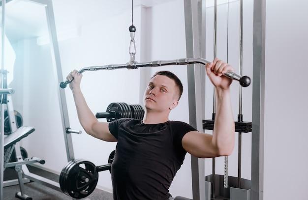 한 남자가 시뮬레이터로 체육관에서 훈련하고 다양한 근육 그룹을위한 운동을합니다. 가슴 갈망, 건강한 운동 몸. 현대 피트니스 클럽