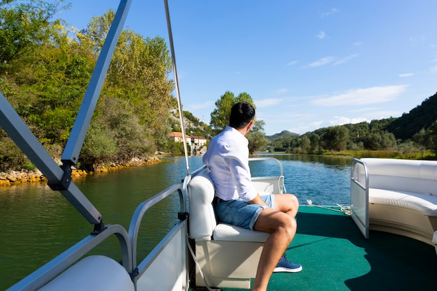男がヨットで山々の間を川に沿って旅する